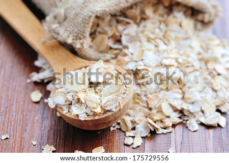 Oat flakes on wooden table - stock photo