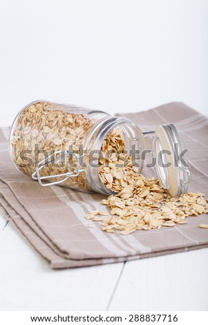Oat flakes spilling out of glass jar. - stock photo