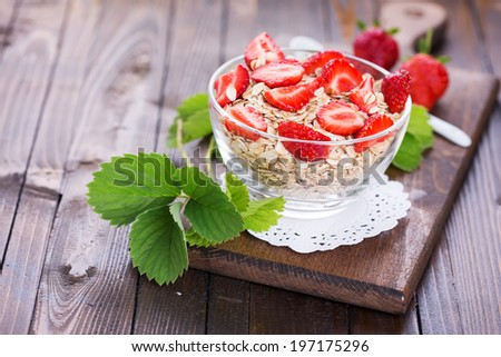 Oat flakes with strawberries  on wooden table. Selective focus. - stock photo