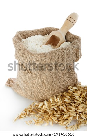 Oat flour in burlap bag on white background - stock photo