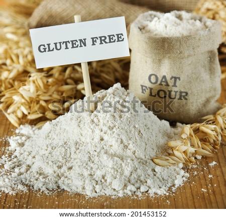 Oat flour on wooden table - stock photo
