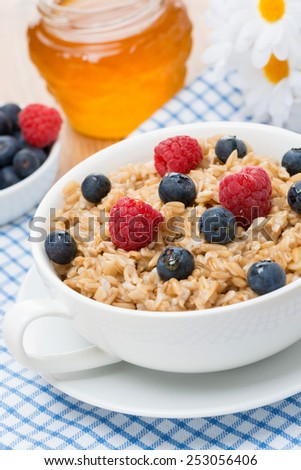 oat porridge with fresh berries, vertical, close-up