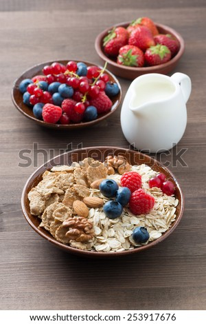 oatmeal and muesli in a bowl, fresh berries and milk on wooden table, vertical, top view - stock photo