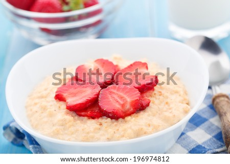 Oatmeal breakfast with strawberries - stock photo