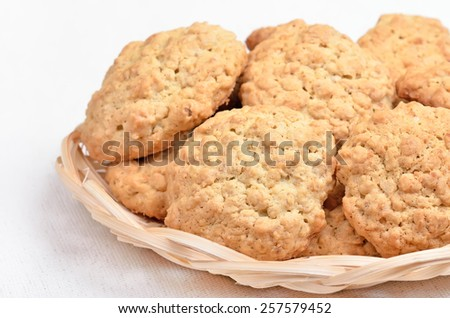 Oatmeal cookies in wicker bowl on white background - stock photo