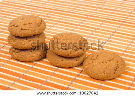 Oatmeal cookies on bamboo table-cloth - stock photo