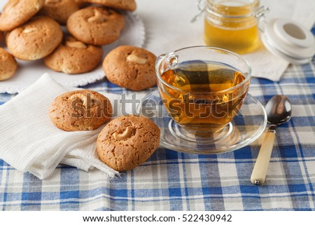 Oatmeal cookies with nut, jar with honey  on napkin on brown wooden table. Food, holiday, cooking, baking background. Concept of home and healthy eating.