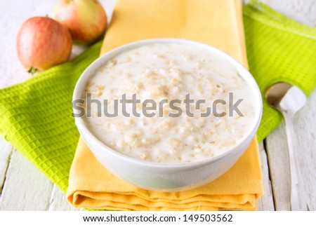 Oatmeal fresh hot simple porridge with spoon on napkin and wooden table. Natural healthy vegetarian breakfast, close up, horizontal. - stock photo