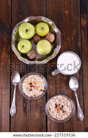 Oatmeal in bowls, yogurt, apples, dried apricots and walnuts on brown wooden background - stock photo