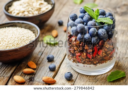 oatmeal nuts quinoa granola with blueberries on a dark wood background. the toning. selective focus - stock photo
