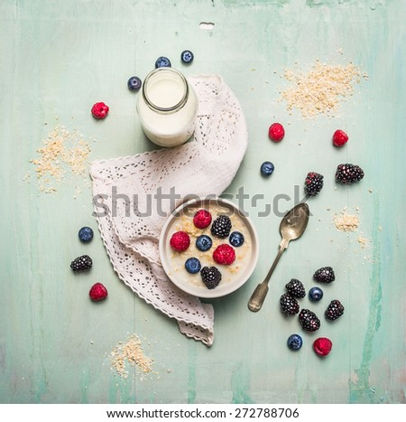 oatmeal porridge, bottle of milk and berries on blue wooden background with kitchen towel, top view - stock photo