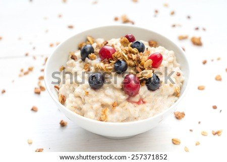 Oatmeal porridge in bowl topped with fresh blueberries, cranberries and homemade crunchy granola  - stock photo