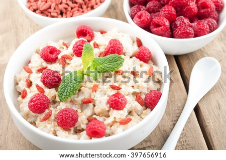 Oatmeal porridge in bowl with raspberries, goji and mint on wooden table closeup. Healthy food for breakfast. Diet, detox and  healthy lifestyle concept - stock photo