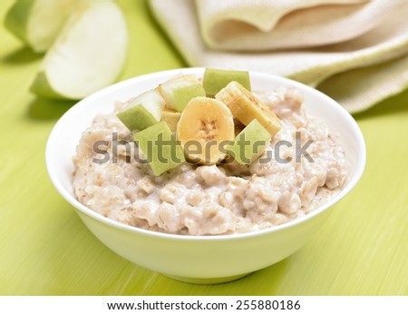 Oatmeal porridge with apple and bananas slices in white bowl on green table - stock photo
