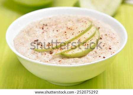 Oatmeal porridge with apple slices and cinnamon in white bowl, close up view - stock photo
