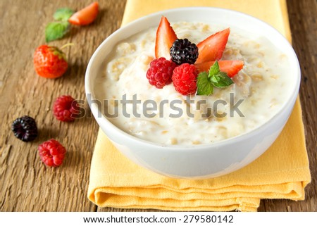 Oatmeal porridge with berries on rustic wooden table - stock photo