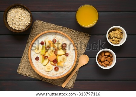 Oatmeal porridge with grape, apple and banana in wooden bowl, walnut, almond, raw oatmeal, fresh juice and wooden spoon on the side, photographed overhead on dark wood with natural light