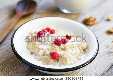 Oatmeal porridge with raspberries and milk on textured wooden table, country style healthy breakfast, Selective focus - stock photo