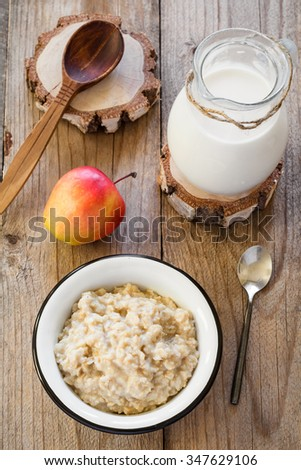 Oatmeal porridge with raspberries, walnuts, red apple and milk on textured wooden table, country style healthy breakfast. Top view, vertical composition - stock photo