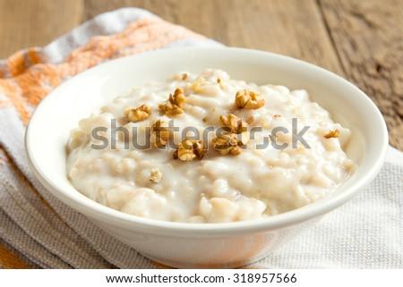 oatmeal porridge with walnuts in white bowl for breakfast - stock photo
