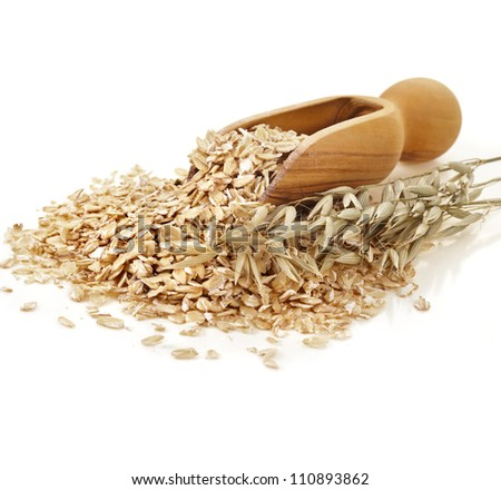 Oatmeal rolled flakes with wooden scoop on white background - stock photo