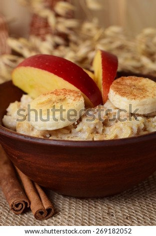 Oatmeal with banana, apple and cinnamon in the bowl and cinnamon sticks on sackcloth