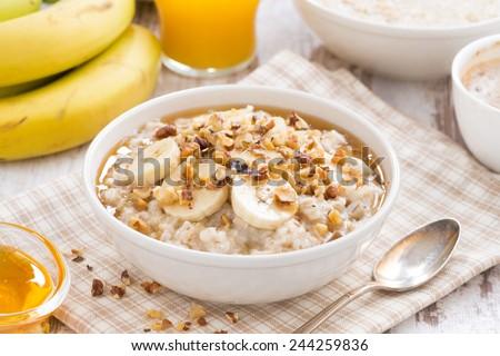oatmeal with banana, honey and walnuts for breakfast, close-up - stock photo