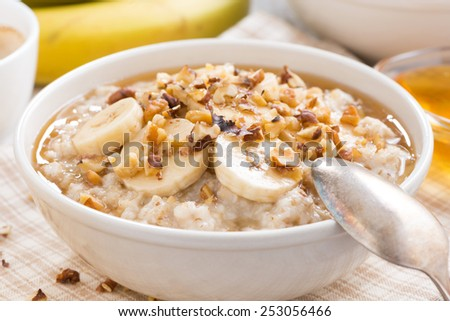 oatmeal with banana, honey and walnuts in bowl for breakfast, close-up, horizontal - stock photo