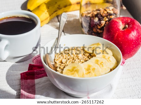 oatmeal with bananas, apples, nuts and dried fruit jar, cup of coffee, healthy breakfast - stock photo