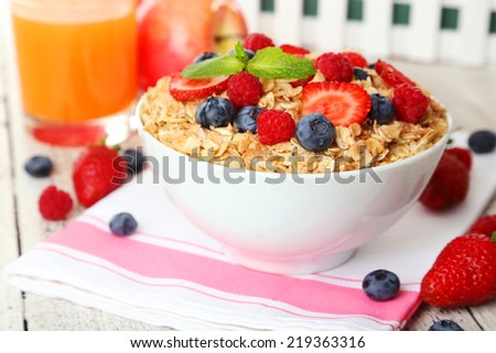 Oatmeal with berries on white wooden background