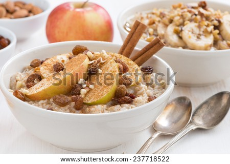 oatmeal with fresh apples, raisins and cinnamon for breakfast on table, close-up, horizontal - stock photo