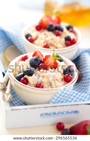Oatmeal with fresh fruits and honey in small bowls on tray.