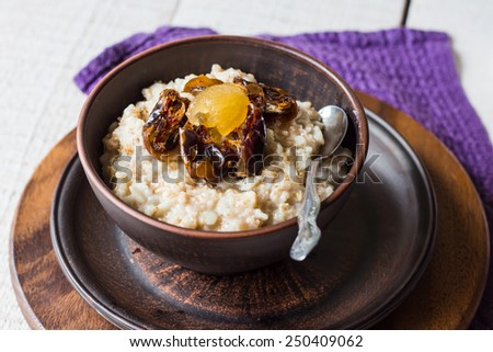 oatmeal with milk and honey and dried fruit, healthy breakfast, on a white background - stock photo