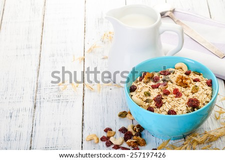 oatmeal with nuts and dried fruits on old white painted wooden table. Perfect breakfast