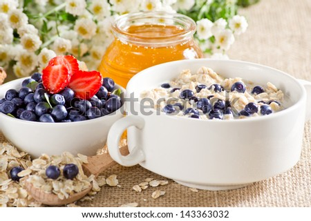Oatmeal with strawberries and blueberries in the bowl, honey and flowers