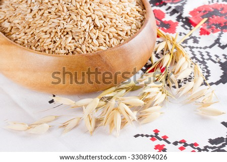 Oats in a wooden bowl and ears of corn oats on the table