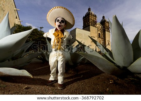 OAXACA, MEXICO, OCTOBER 30, 2014: a kid dressed up as a charro plays in front of Santo Domingo church before the comparsa starts  - stock photo