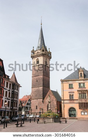 OBERNAI, FRANCE - MAY 11, 2015: Chapel tower, Sainte Odile fountain and town hall on the market square of Obernai, Bas-Rhin, Alsace, France - stock photo
