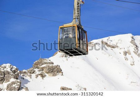 Oberstdorf, Germany - December 23, 2015: Nebelhorn cable car moving up Nebelhorn Mountain in winter time. The cable car offers close views of the Nebelhorn summit.   - stock photo