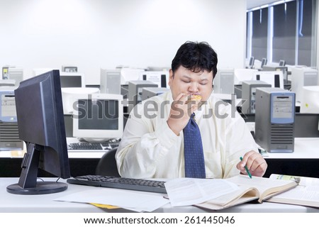 Obese entrepreneur working on table while biting a burger, shot in the office - stock photo