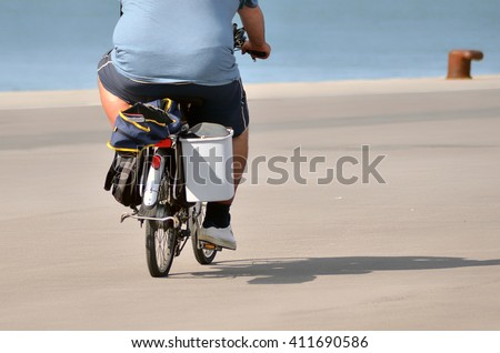obese person cycling on the road in spring - stock photo