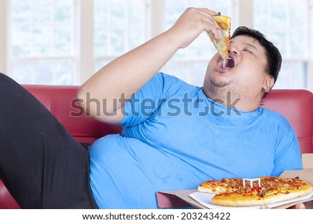 Obese person eats pizza while sitting on couch at home - stock photo