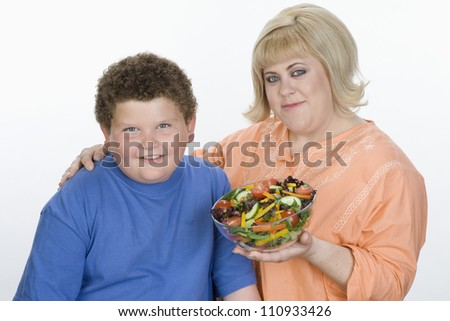 Obese teenage boy and mother with a bowl of salad isolated over white background - stock photo