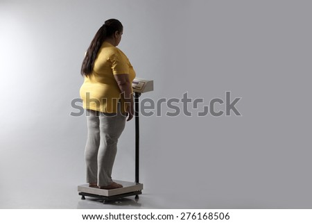 Obese woman checking her weight - stock photo