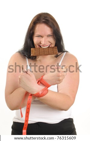 Obese woman with long black hair holding a chocolate bar in his hand and puts them to eat in front of white background.