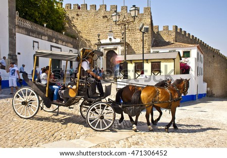 OBIDOS, PORTUGAL - AUG 16,2016: Coach with tourists during a  sidewalk on Aug 14, 2016 in Obidos, Portugal. Horse carriage is a popular way for sightseeing in Obidos village.