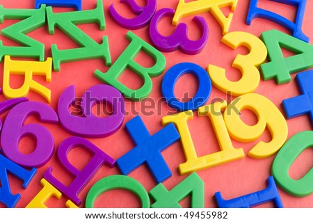 object on red - toy plastic letters and numbers