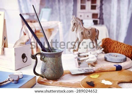 Objects and tools of creative hobby, paintbrush, wooden horse on a table in vintage style, - stock photo