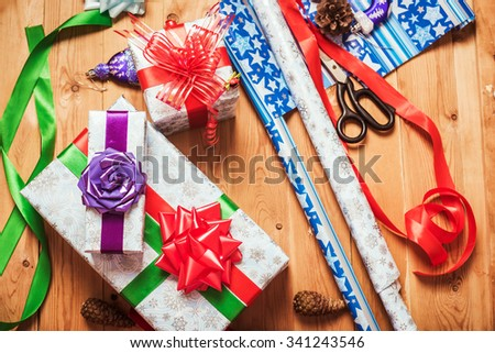 Objects for wrapping Christmas presents on wooden background - stock photo