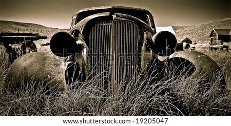 Objects in various stages of decay and aging, abandoned and forgotten - vintage Chevy. - stock photo